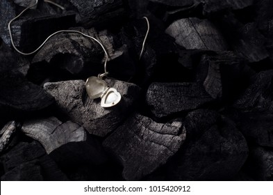 Silver heart shape locket with necklace on black charcoal texture background