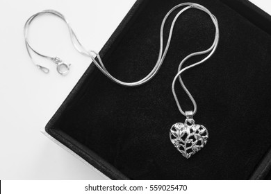 Silver heart shaped medallion in black jewel box