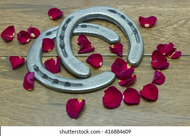 Silver horseshoes on barn wood background with red rose petals.