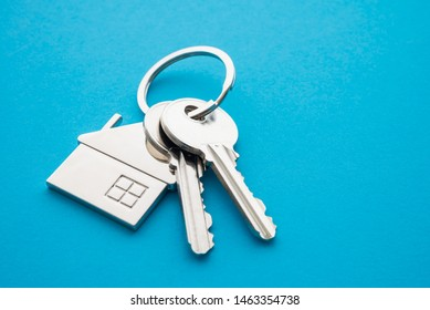 Silver house key with house keychain on blue background with copy space. Dream new house buying, real estate property business concept.