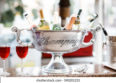 Silver ice cooler bucket with wine and champagne bottles on a marble bar in a restaurant