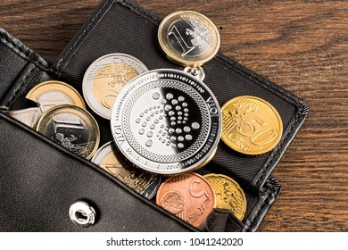 silver iota crypto currency coin on euro coins in leather wallet on wooden background
