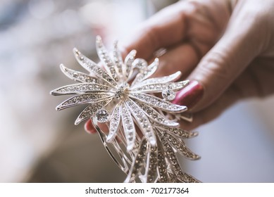 Silver jewel with diamonds in a woman's hand