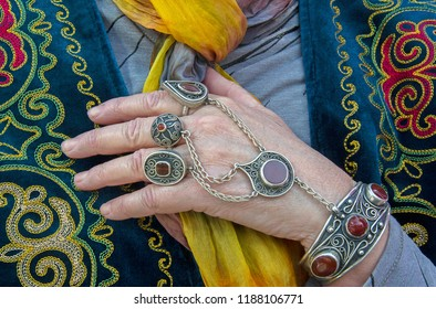Silver jewelry in Kazakh style on older woman's hand against national costume. Bracelet & rings traditionally fixed for nomadic life (to keep jewel while riding horse)
