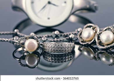 silver jewelry with pearls on a background of elegant women's watches