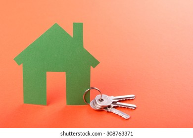 Silver key with green house figure. Real Estate Concept.