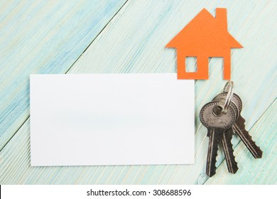 Silver key with house figure and blank business card on wooden background. Real Estate Concept. Top view.