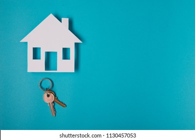 Silver key with house figure on blue background. Top view.