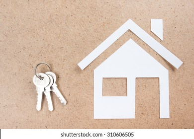 Silver key with house figure and on wooden background. Real Estate Concept. Top view.