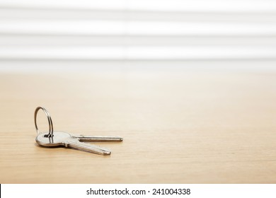the silver key on the wood office desk(table) behind white blind.