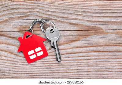 Silver key with red house figure on wooden background