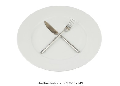 silver knife and fork crossed on a white plate on white - gray background with light shaddow