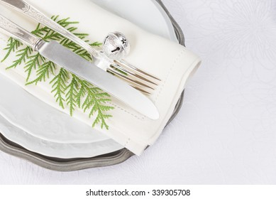 Silver knife and fork jingles and green thuja branches lie on the white porcelain plate, which is located on a table covered with a white tablecloth