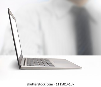 Silver laptop with blank monitor screen on the white table, side view.