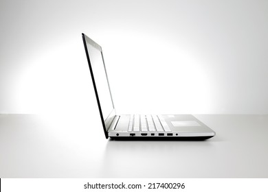 Silver laptop computer side view with spot backlight