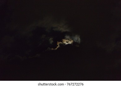Silver lining of the moon behind a night cloud.