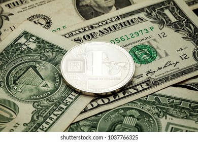 Silver Litecoin Cryptocurrency coin on a pile of US dollars, cash money and cryptocurrency concept