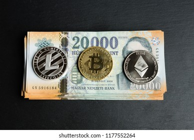 Silver litecoin, ethereum and golden bitcoin coin on hungarian forint close up. Money concept.