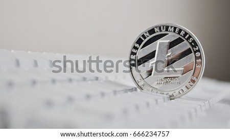Silver Litecoin physical cryptocurrency coin on white commputer keyboard.