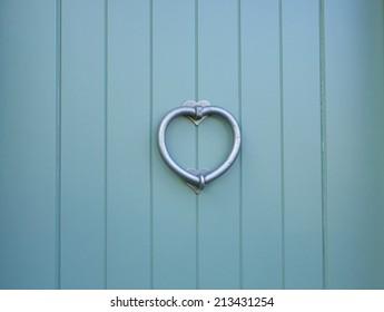 Silver love heart door knocker on a sky blue door