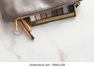 Silver make up bag emptying onto white marble counter with eyeshadow and gold make up brushes. White marble copy space.