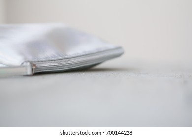 Silver make up bag, faux leather, opened, with beauty supplies: pink kabuki brush, lipstick, mirror. Light grey background. Clean and minimal composition, copyspace. Blurred image, selective focus.