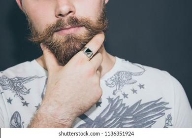 Silver male ring of the seal, on the hand of a bearded man with a mustache.