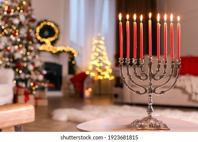 Silver menorah on white table in room with fireplace and Christmas decorations. Hanukkah symbol