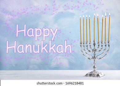 Silver menorah on white wooden table. Happy Hanukkah!