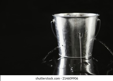 Silver metal bucket full of holes leaking water with jets of water spurting out onto a reflective black background with copyspace in a conceptual image