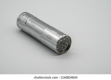 Silver metal damaged flashlight isolated on white background