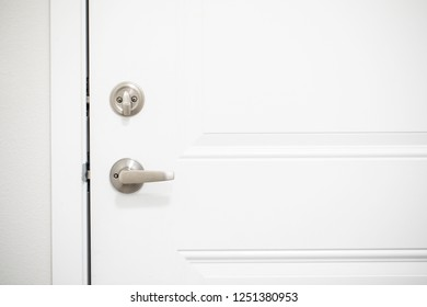 Silver metal deadbolt lock on a white door