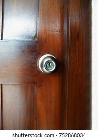 Silver metal door knob on wooden door
