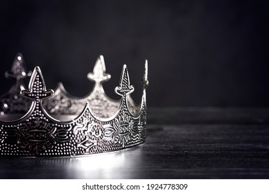 A Silver Metal King or Queens Crown on a black Wood Table