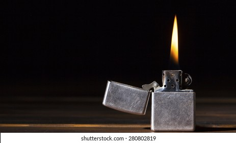 Silver Metal Lighter On Black Background With Flame