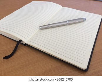 Silver metal pen on notepad