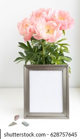 silver metal photo frame mock-up with bouquet of peonies and little stones