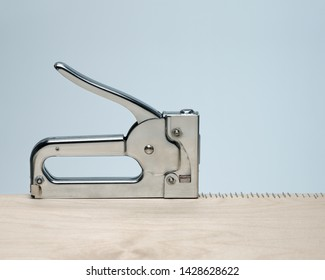 Silver metal stapler creates precise row of staples in pale wood surface with blue background.  Concept obsession, compulsion, repetitive.