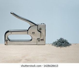 Silver metal stapler malfunctions creating precise row and random pile of staples in pale wood surface on blue background. Concept obsession, compulsion, malfunction.