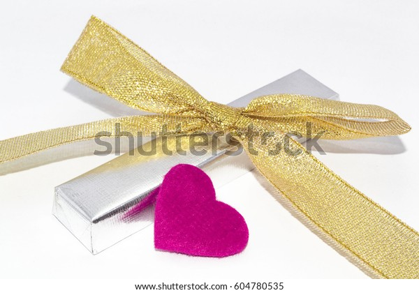 Silver metallic foil wrapped chocolate bar. Gentle gold bow with bright purple heart. White background