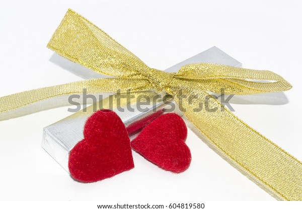 Silver metallic foil wrapped chocolate bar. Gentle gold bow with bright red hearts. White background