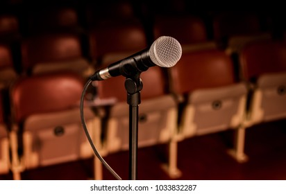 Silver microphone and stand on a stage of a theater