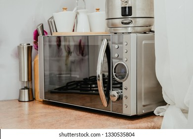 Silver microwave in the kitchen. A modern and designer microwave stands on the kitchen counter. The concept of heating a meal, reheating food. Fast food preparation.