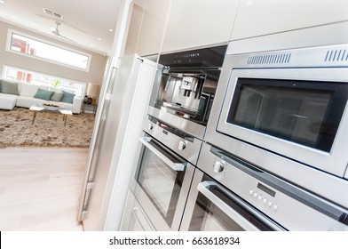 The silver microwave ovens and pantry cupboards installed to the wall of in the kitchen, The refrigerator is fixed next to the oven and under the pantry. these wall oven cabinets are in technology