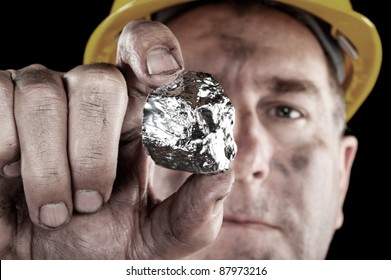 A silver miner shows off his newly excavated silver nugget.