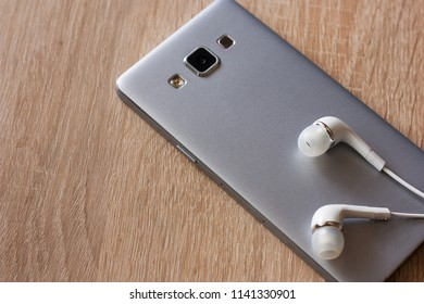 silver modern phone with headphones on a wooden table