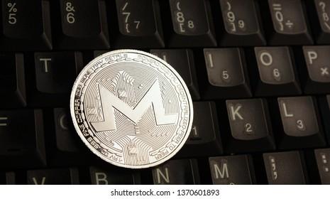 Silver Monero XMR coin on laptop keyboard