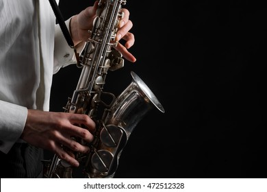 Silver musical instrument in male hands in the process of playing jazz. Expensive vintage saxophone in macro. Accurate fingers of player.