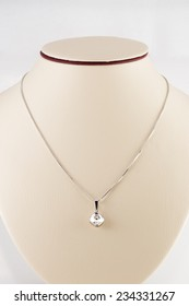Silver necklace and pendant on white mannequin