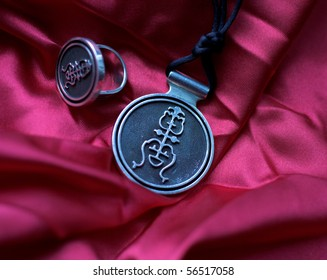 Silver necklace and ring  on the red silk